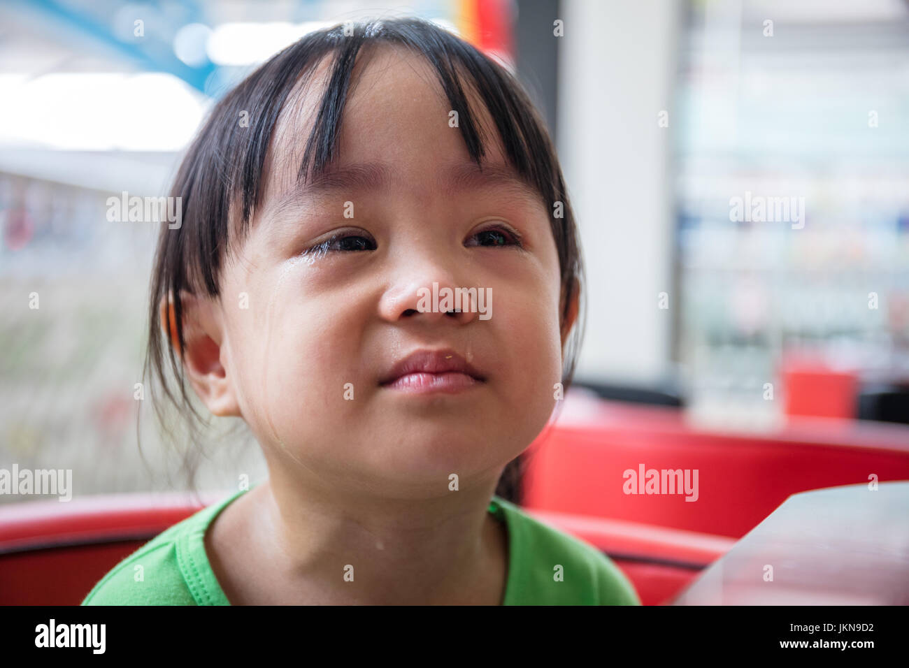 Asian Chinese little girl sitting in chair and crying - Stock Image