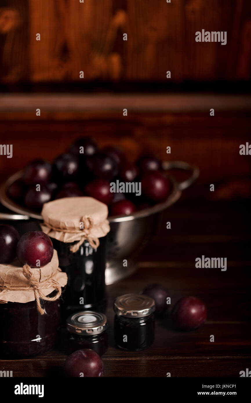 Ripe plums and jars with plum jam on a wooden background. Selective focus. - Stock Image