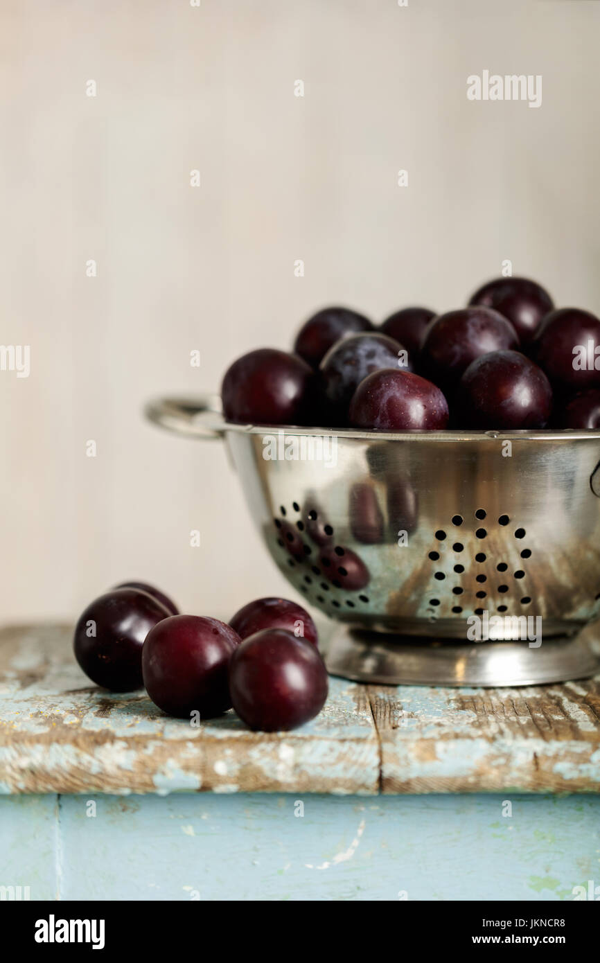 Ripe plums in a colander on a wooden background. Selective focus. - Stock Image