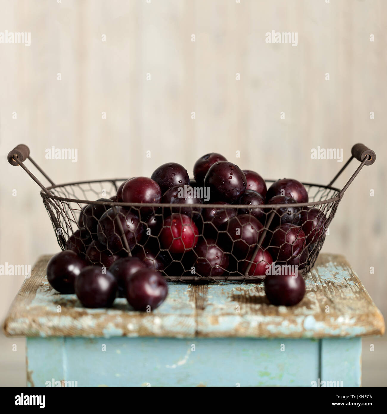 Ripe plums in a basket on a wooden background. Selective focus. - Stock Image