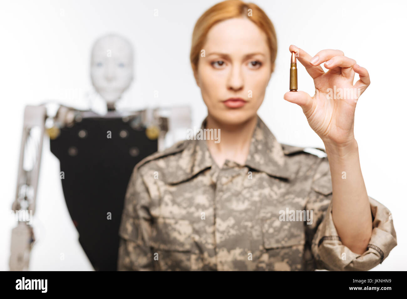 Resolute serious woman holding a bullet - Stock Image