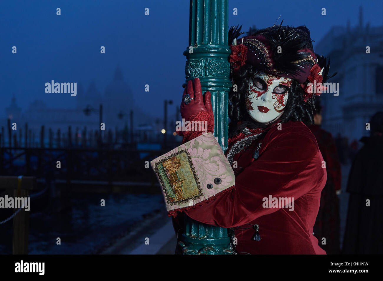 Female Mask wearer at the Carnival of Venice with red Coat and Red dress Stock Photo