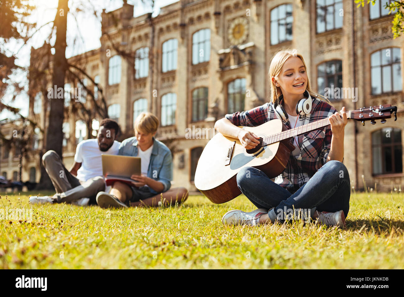 Committed young woman practicing her music skills - Stock Image