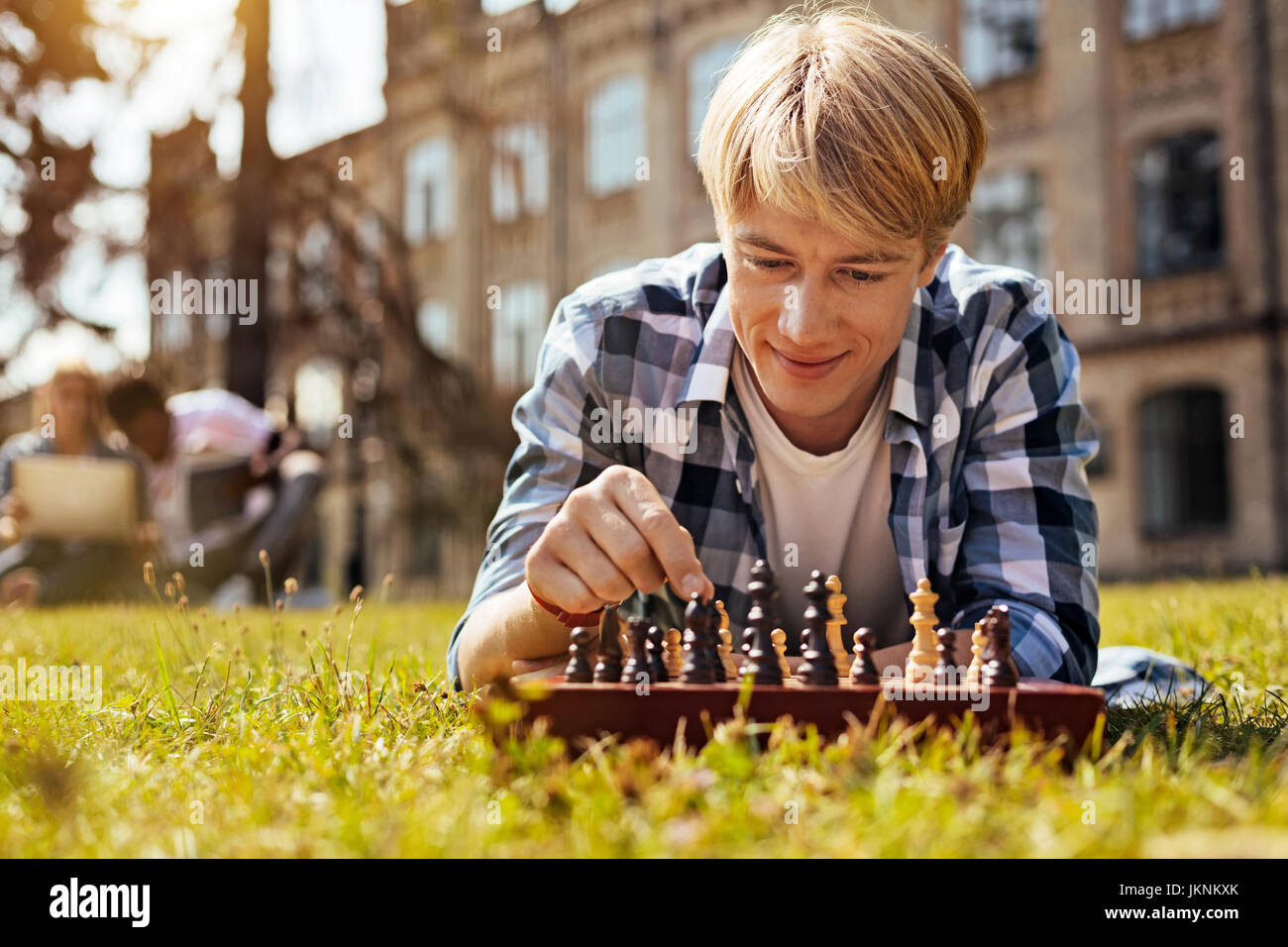 Analytical intelligent man relaxing while playing - Stock Image