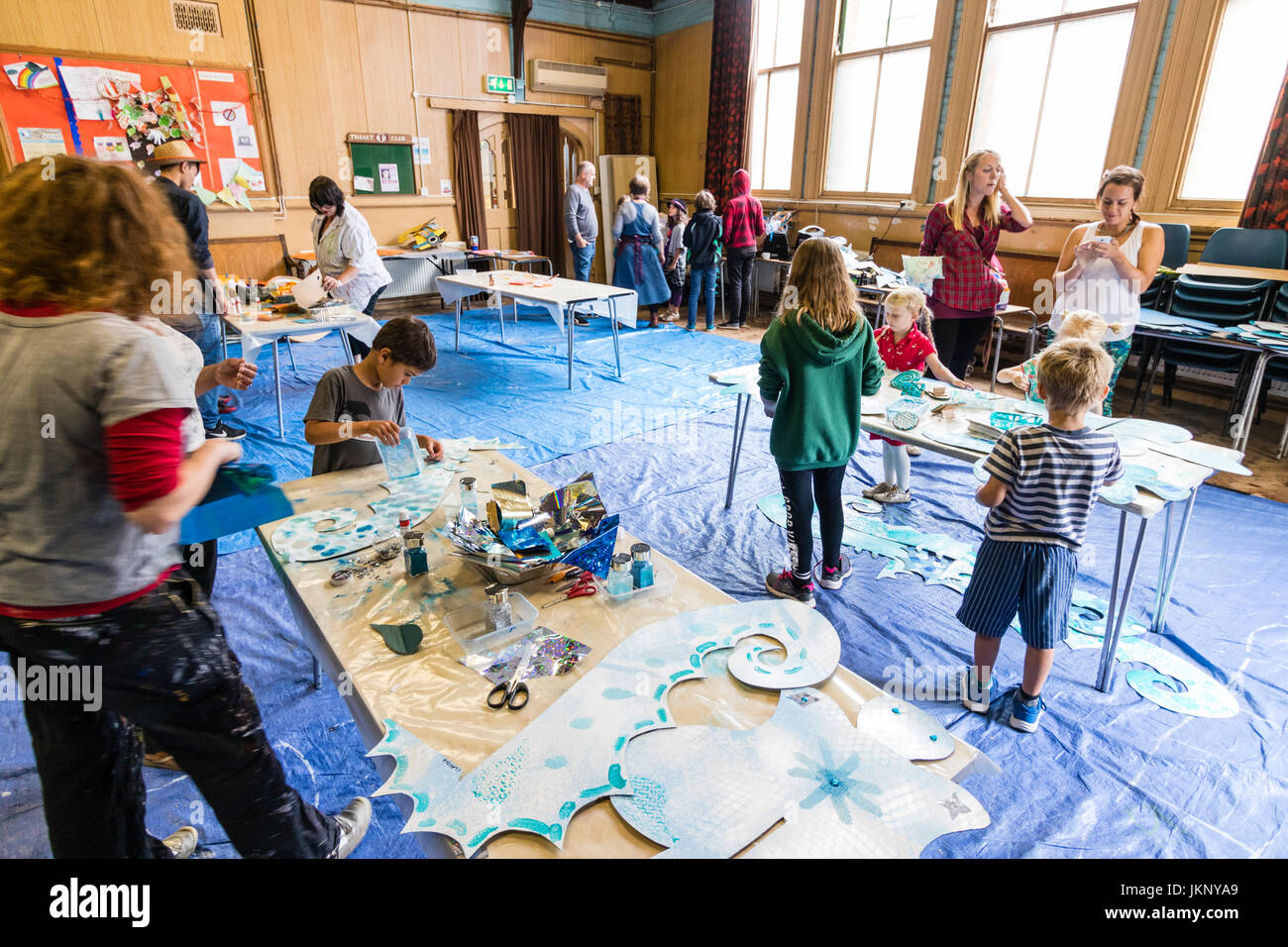 Caucasian adults and children at indoor creative arts and crafts workshop. Children working at tables painting cardboard - Stock Image