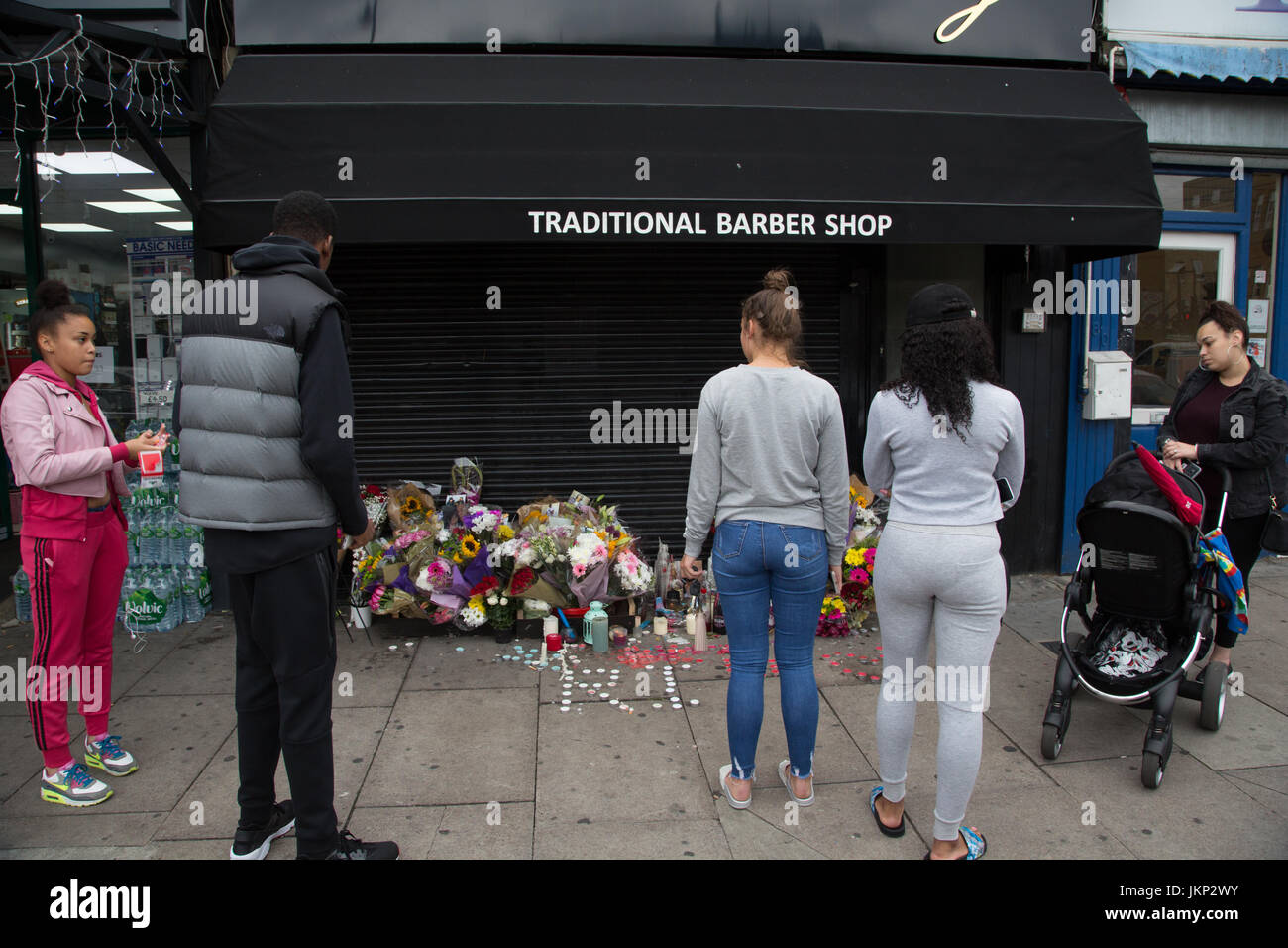 London, UK. 24th July, 2017. People look at floral tributes for Rashan Charles who died after being chased and arrested - Stock Image