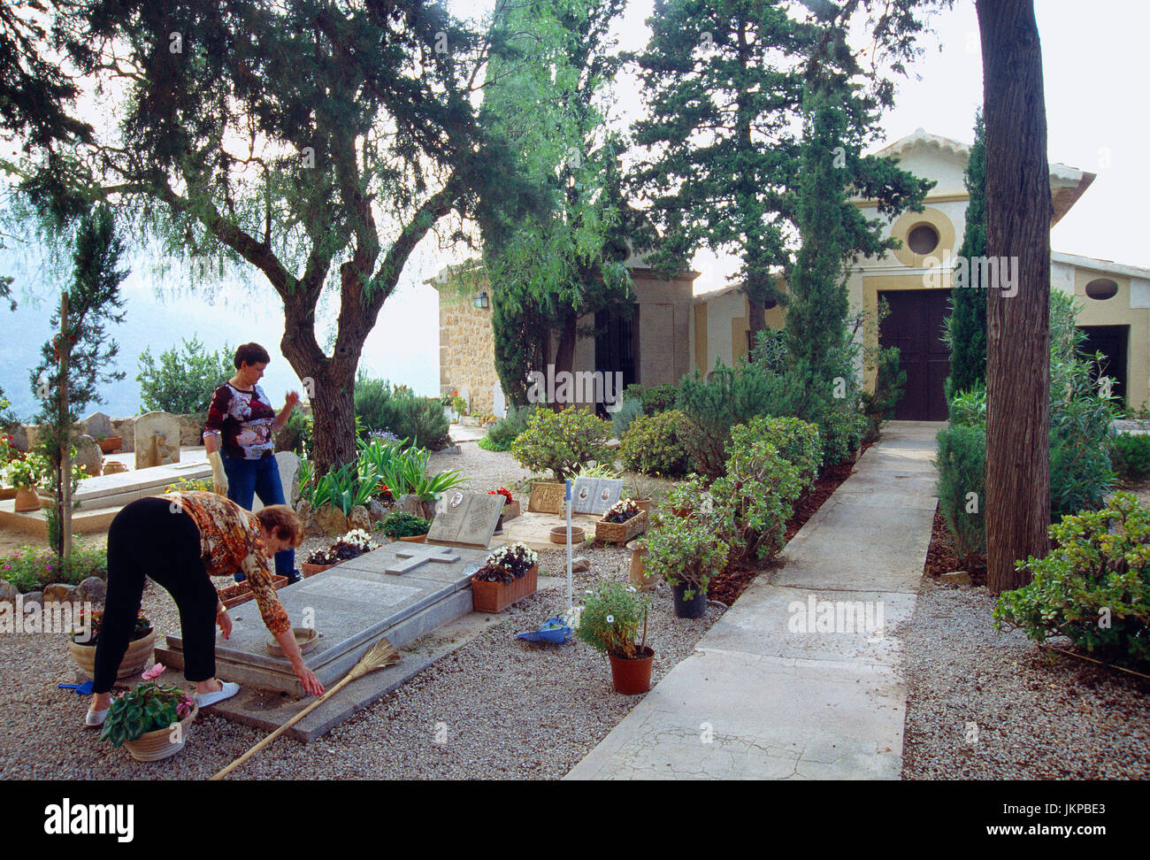 Two women working at the cemetery. Deia, Mallorca island, Balearic Islands, Spain. - Stock Image