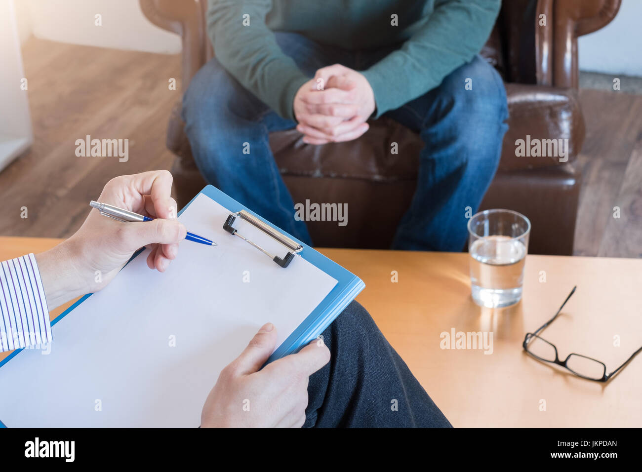 Psychologist taking notes during psychotherapy session Stock Photo