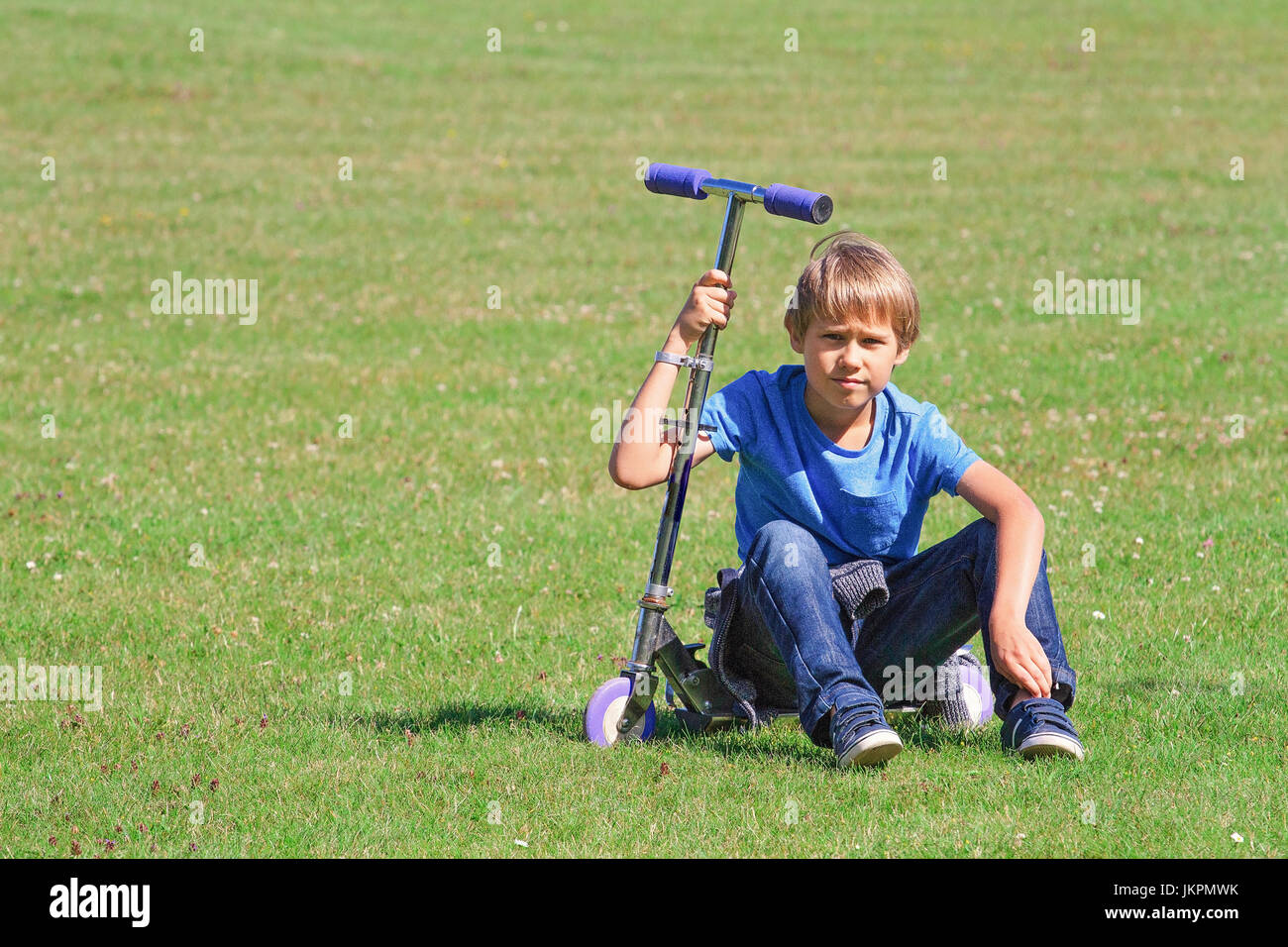 Boy sitting on a scooter in the park - Stock Image