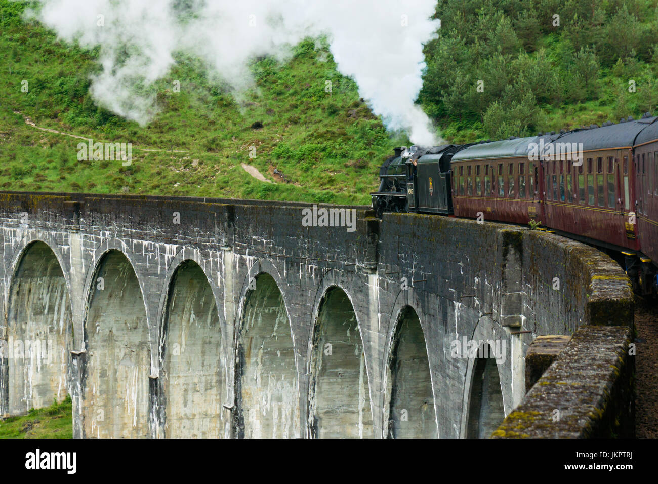 The Jacobite steam train on the Glenfinnan (Glenfinan) viaduct as seen in the harry potters movies. Viaduct in the - Stock Image