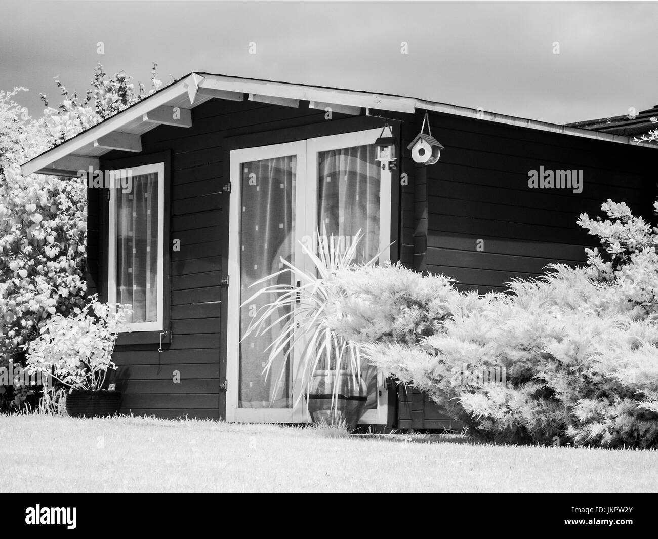A chalet style wooden garden shed taken on an infrared converted camera. - Stock Image