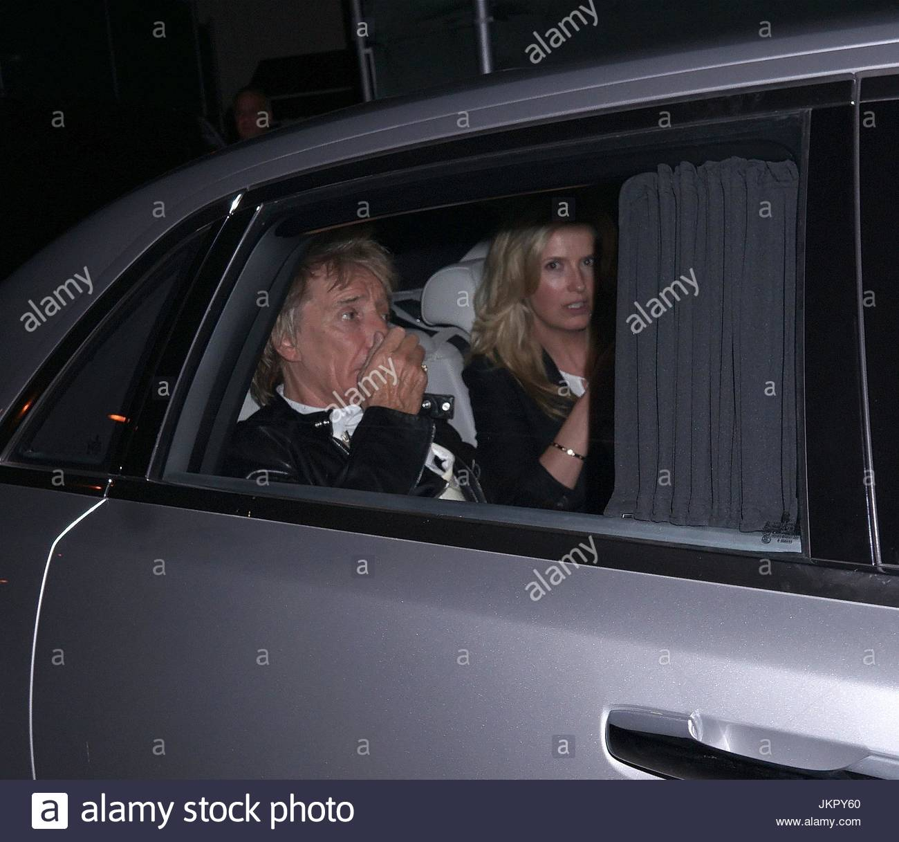 Rod Stewart and Penny Lancaster. Rod Stewart left through back door with wife Penny Lancaster. As they drove off Rod can be seen holding his nose. & Rod Stewart and Penny Lancaster. Rod Stewart left through back door ...