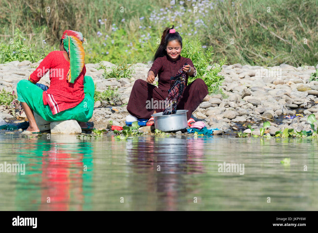 Nepalese women washing clothes in a river, For editorial Use only, Chitwan district, Nepal - Stock Image