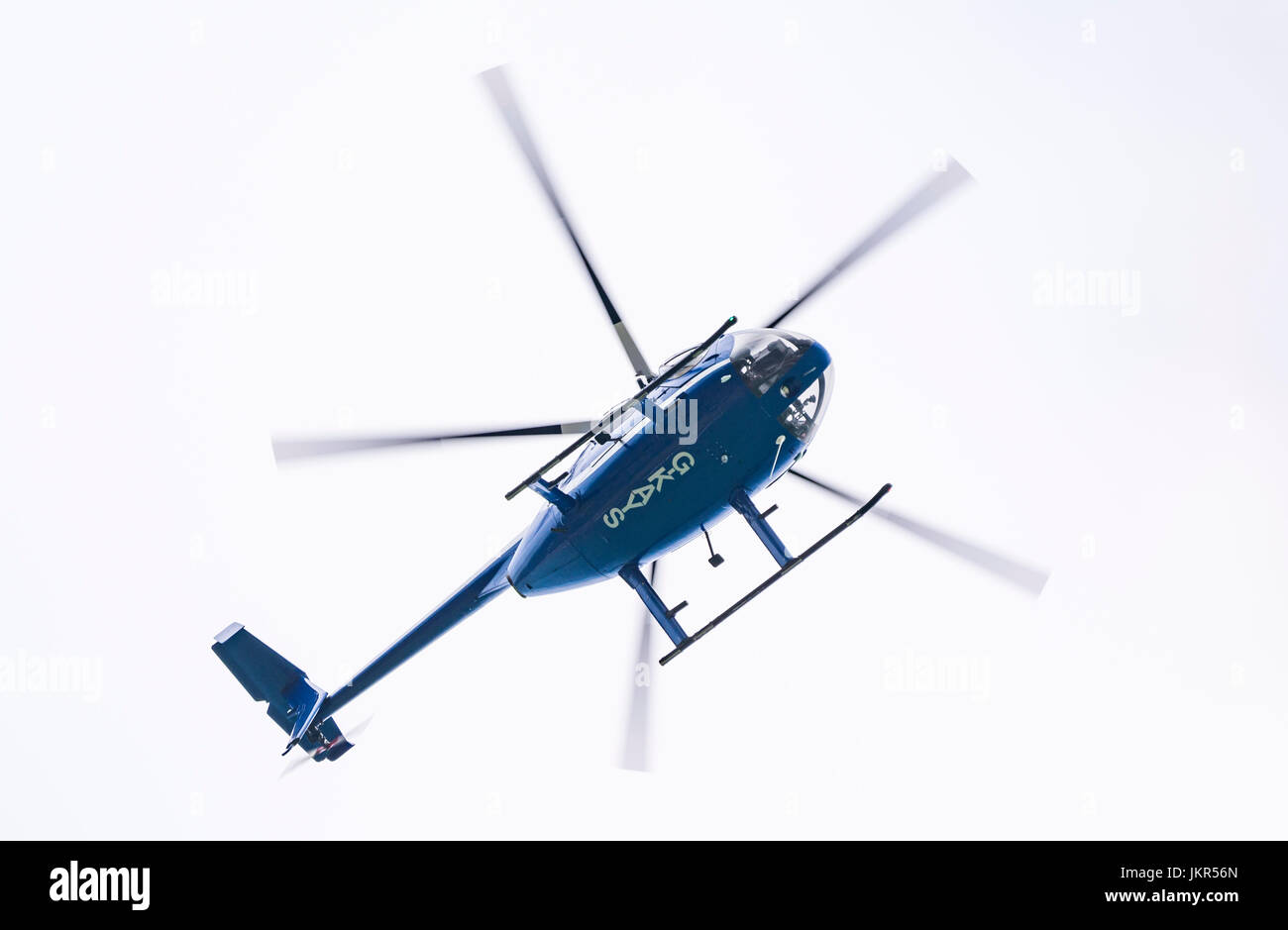 Looking up at a low flying helicopter. - Stock Image