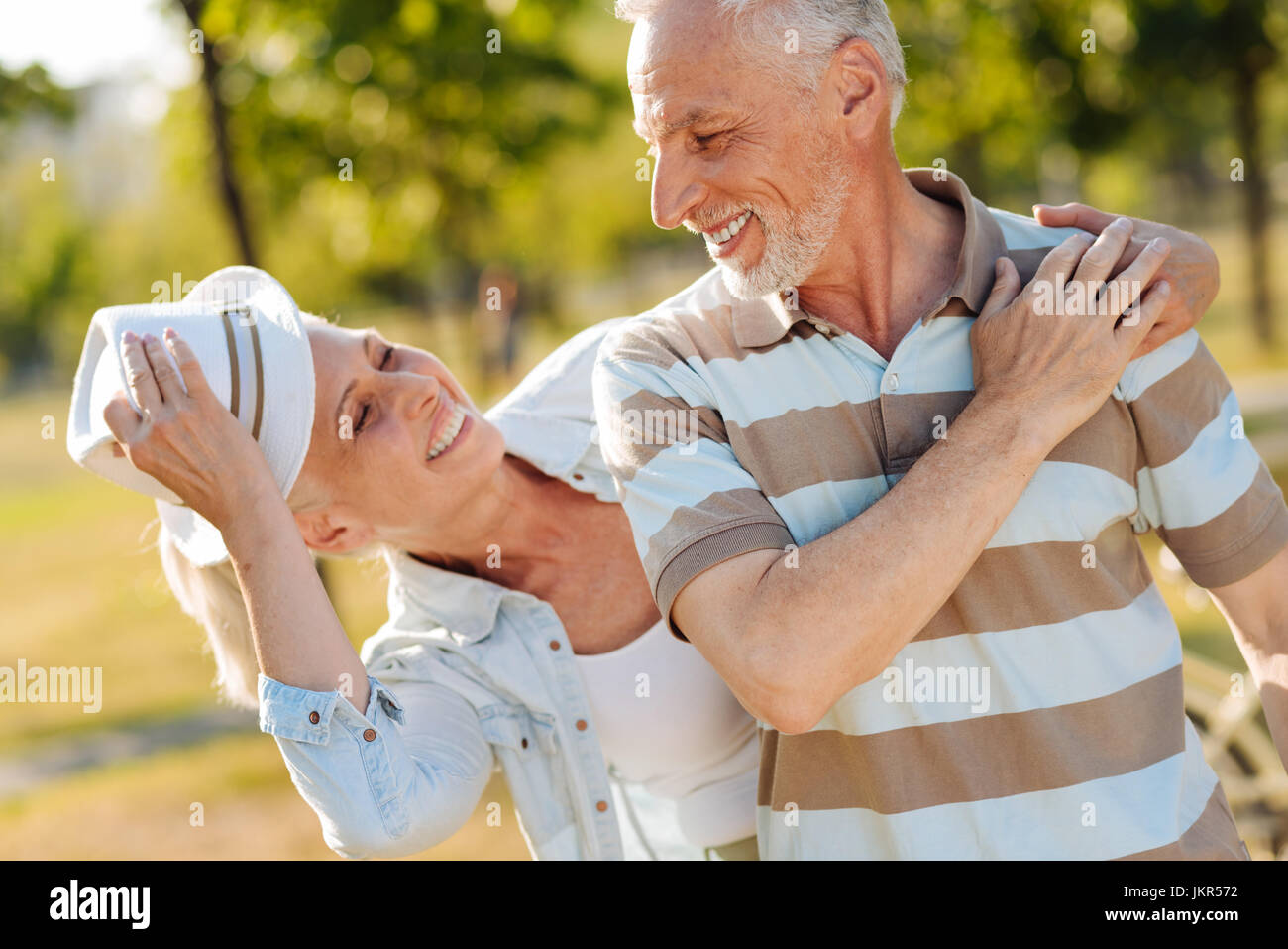 Joyful mature people playing tricks together - Stock Image