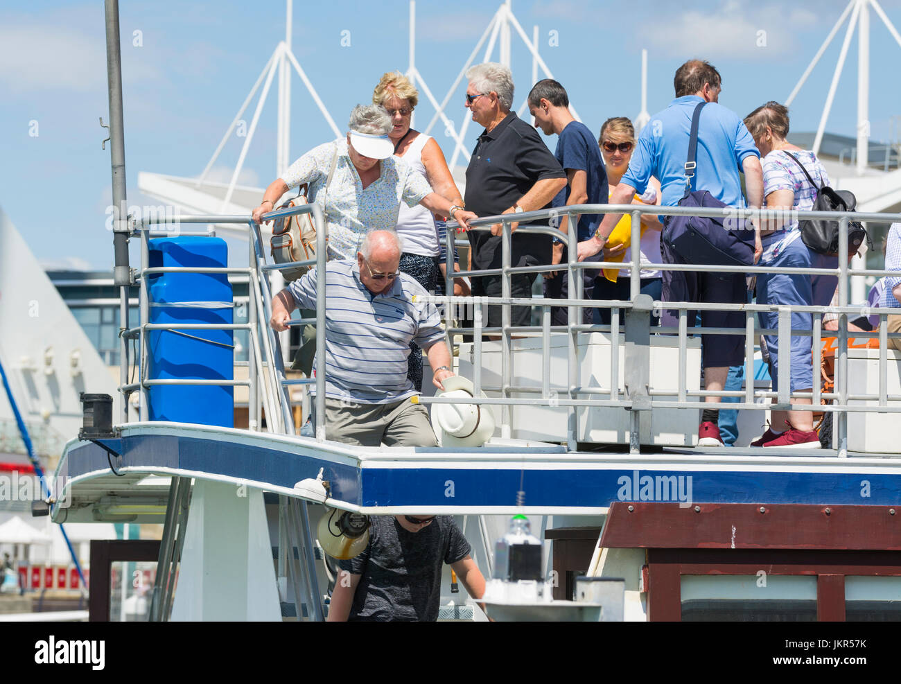 Ferry passengers disembarking from a boat. - Stock Image