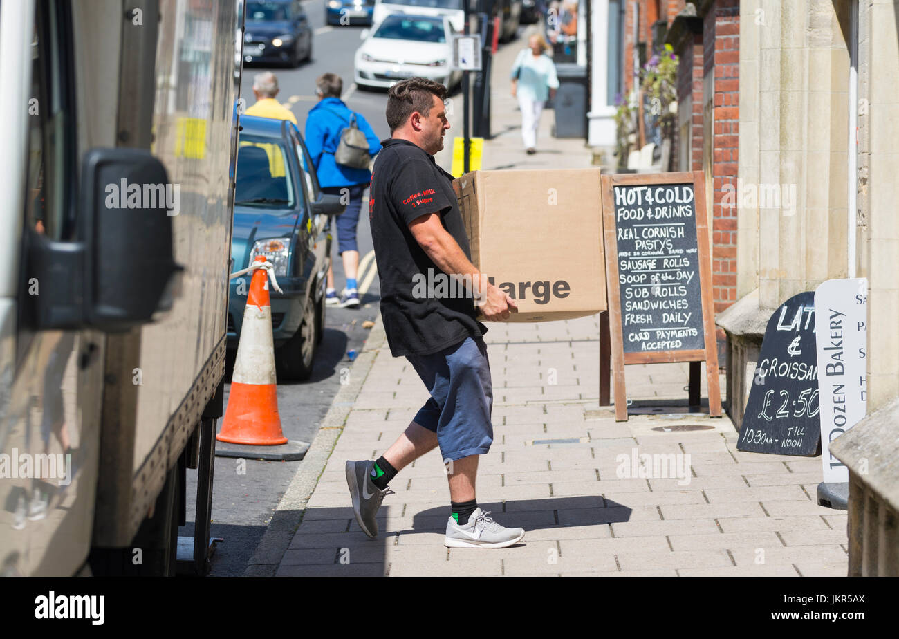 Man making a delivery, carrying a heavy box from a van. - Stock Image