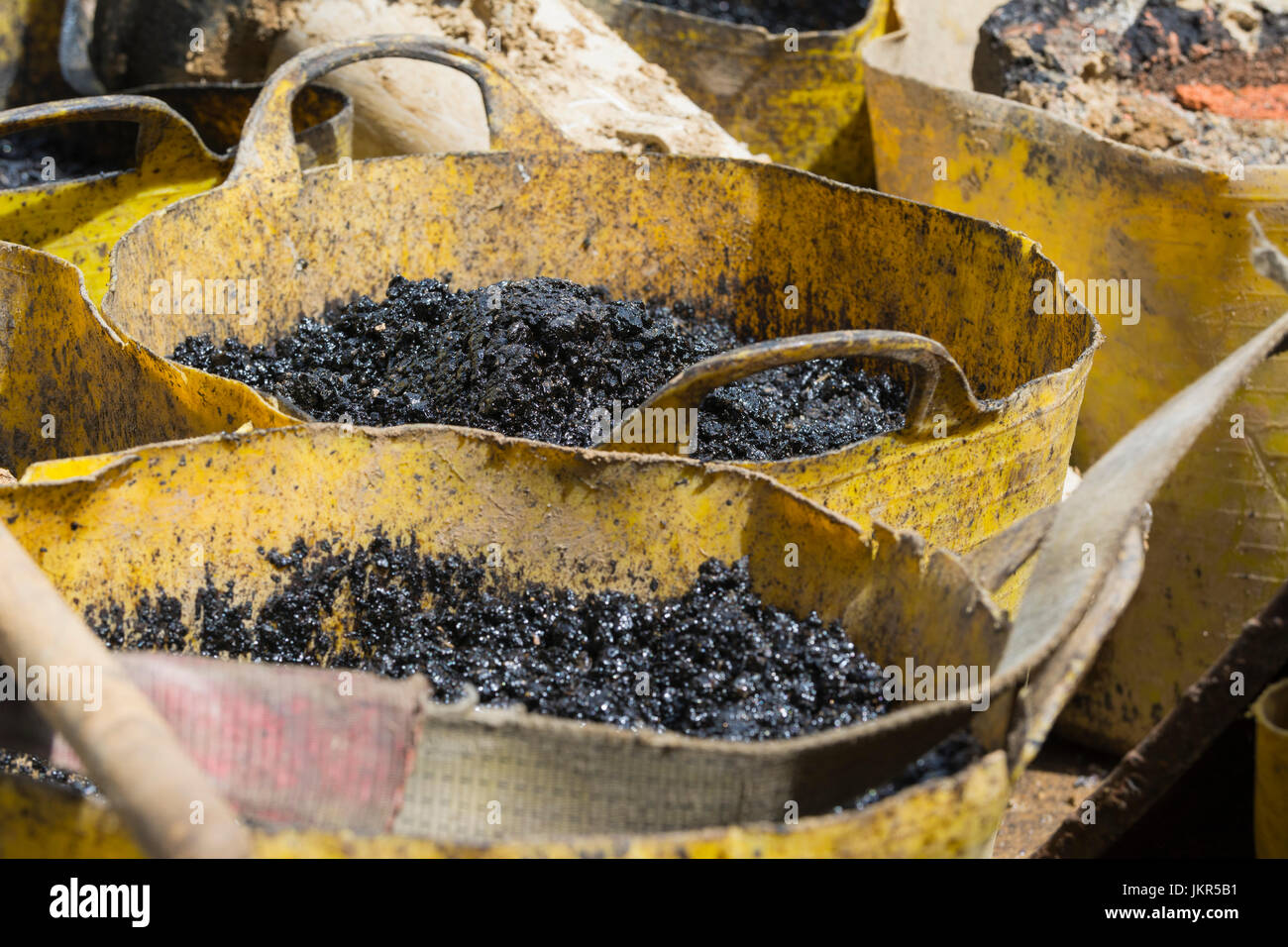 Bitumen in buckets on a construction site ready for use in road resurfacing. AKA Asphalt and Tar. - Stock Image