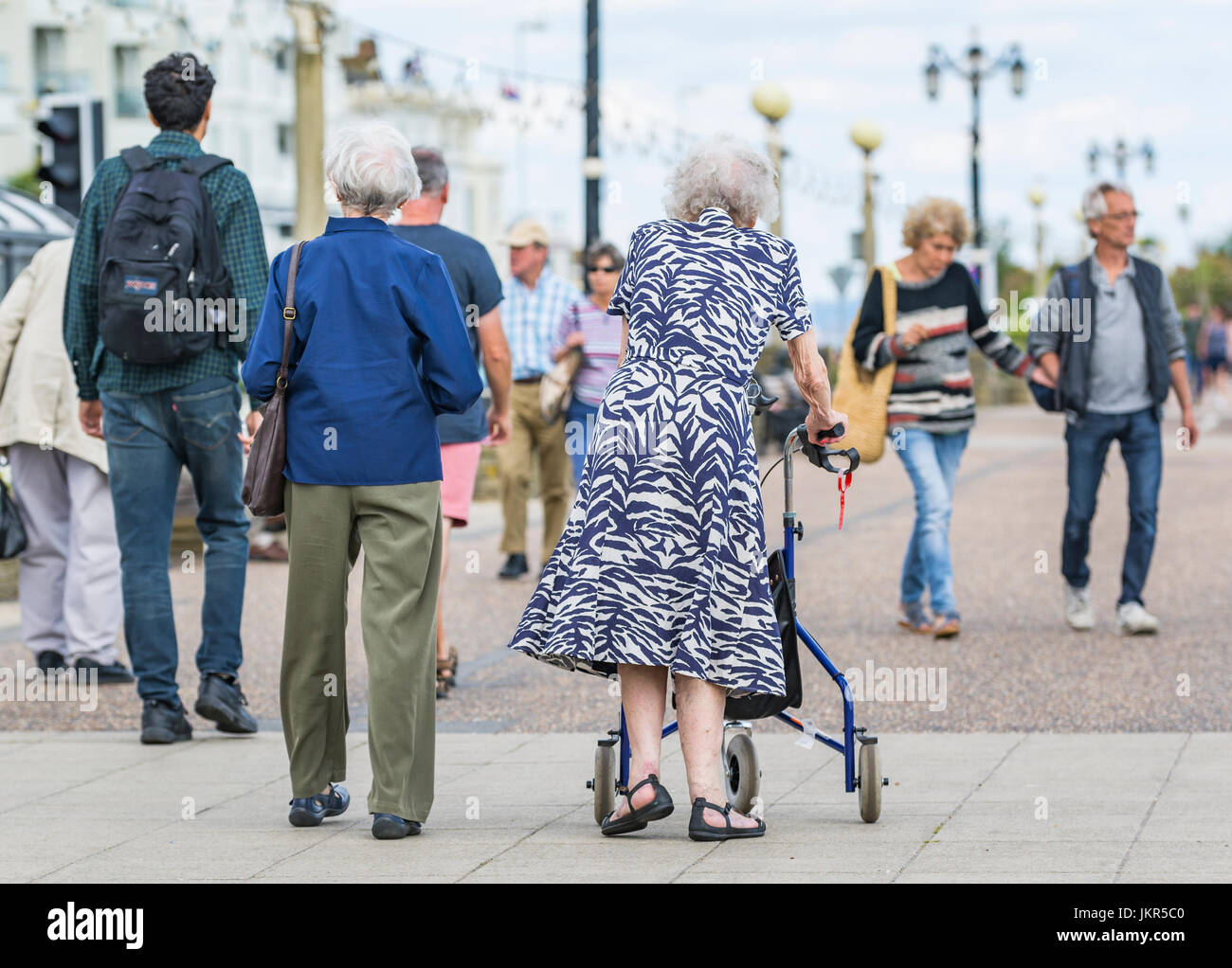 Rollator walking aid. Elderly woman walking with a wheeled walking frame or wheeled Zimmer frame in England, UK. - Stock Image