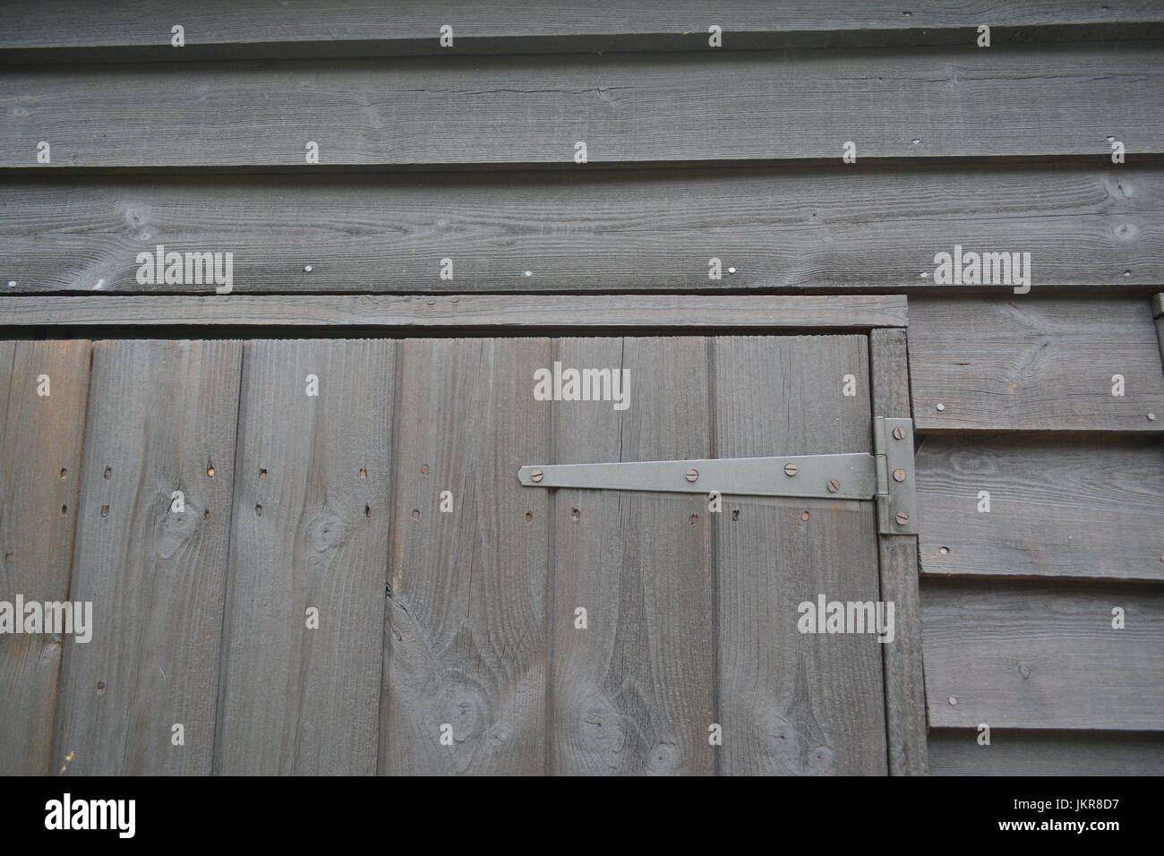 Close up of timber shed showing detailing of overlapping wood door and hinge re wood treatment creocote maintenance - Stock Image