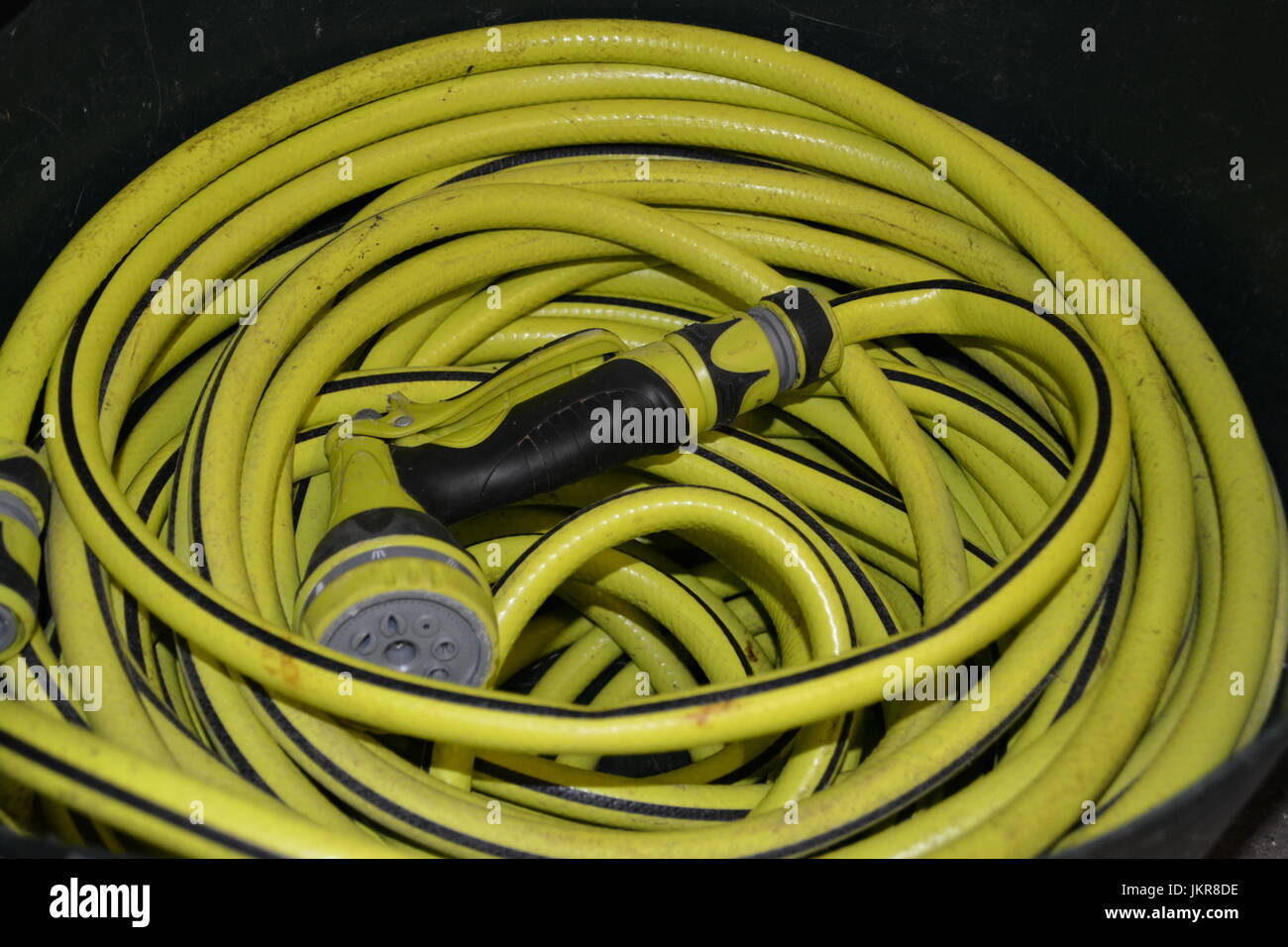 Close up of long length coiled hose hosepipe with multi spray hose gun watering nozzle attachment re watering the - Stock Image