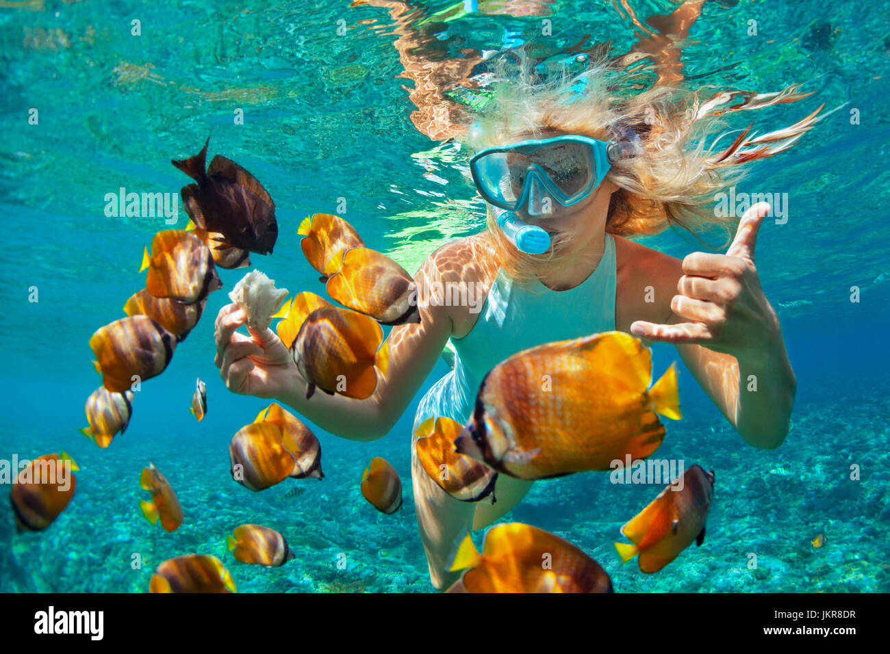 Happy family - girl in snorkeling mask dive underwater with tropical fishes in coral reef sea pool. Travel lifestyle, - Stock Image