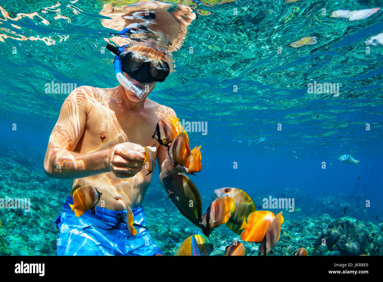 Happy family vacation - man in snorkeling mask dive underwater with tropical fishes in coral reef sea pool. Travel - Stock Image