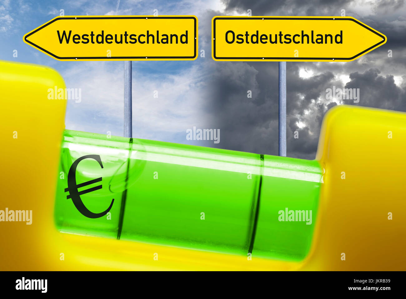 Spirit level in the imbalance, unequal salaries in west country and Eastern Germany, Wasserwaage im Ungleichgewicht, - Stock Image