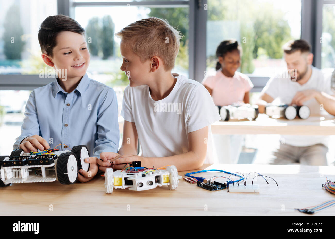 Two pre-teen students socializing during robotics class - Stock Image