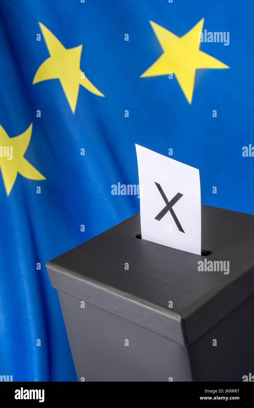 Blue and yellow EU flag with miniature black ballot box and voting paper - as metaphor for the European Parliament - Stock Image