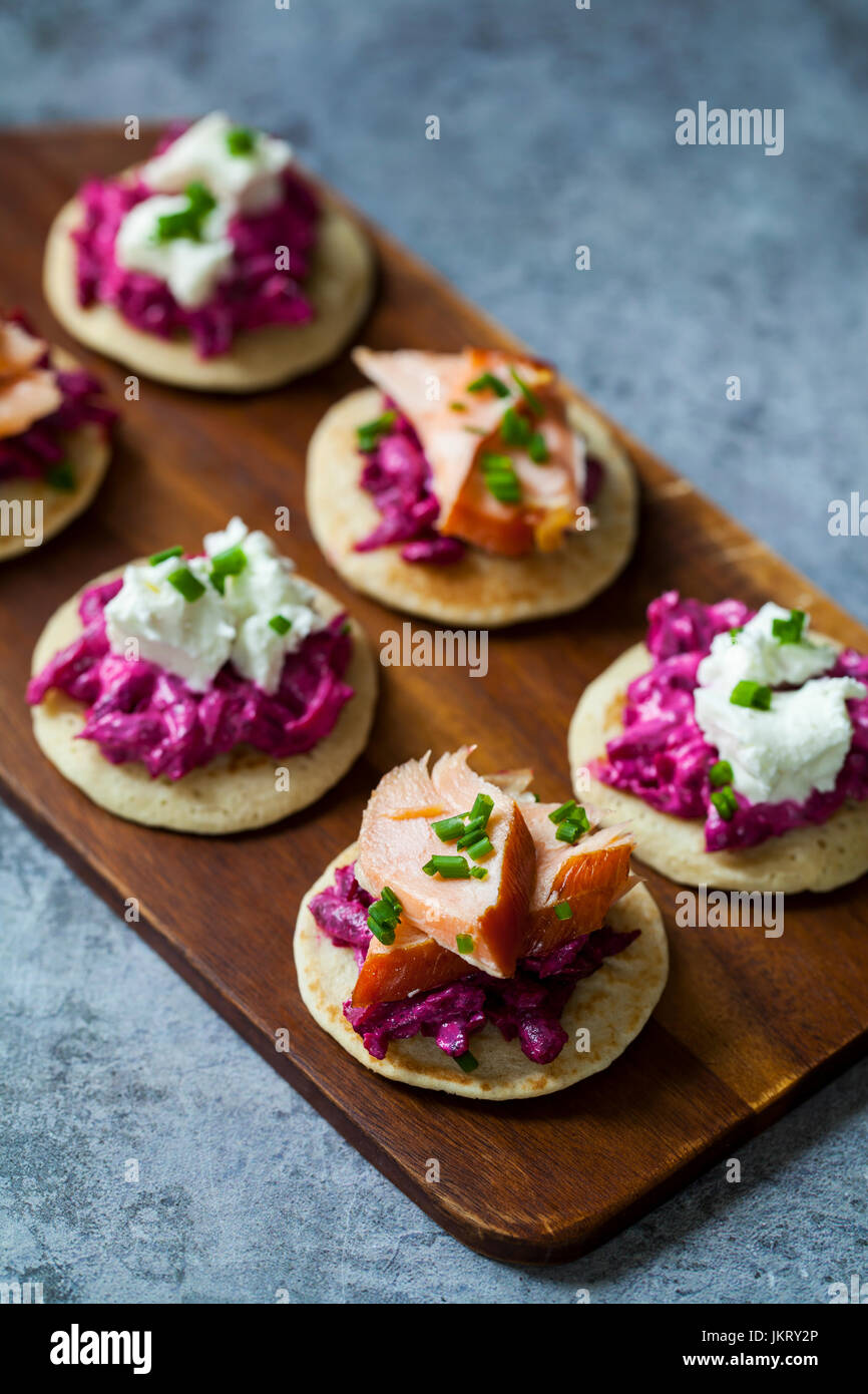 Blinis with beetroot, horseradish, hot smoked salmon and goat chhese - Stock Image