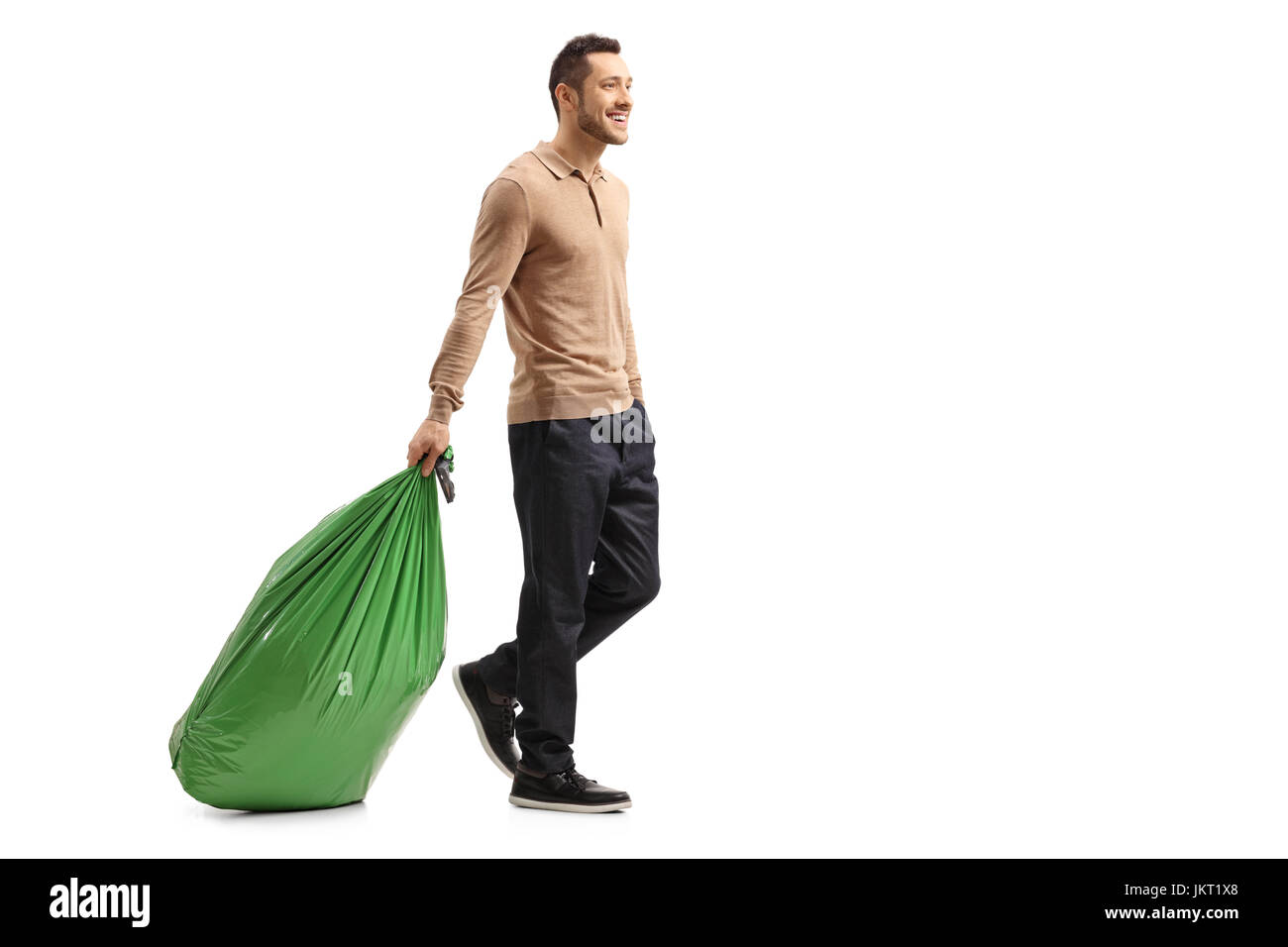 Full length profile shot of a guy dragging a garbage bag isolated on white background - Stock Image