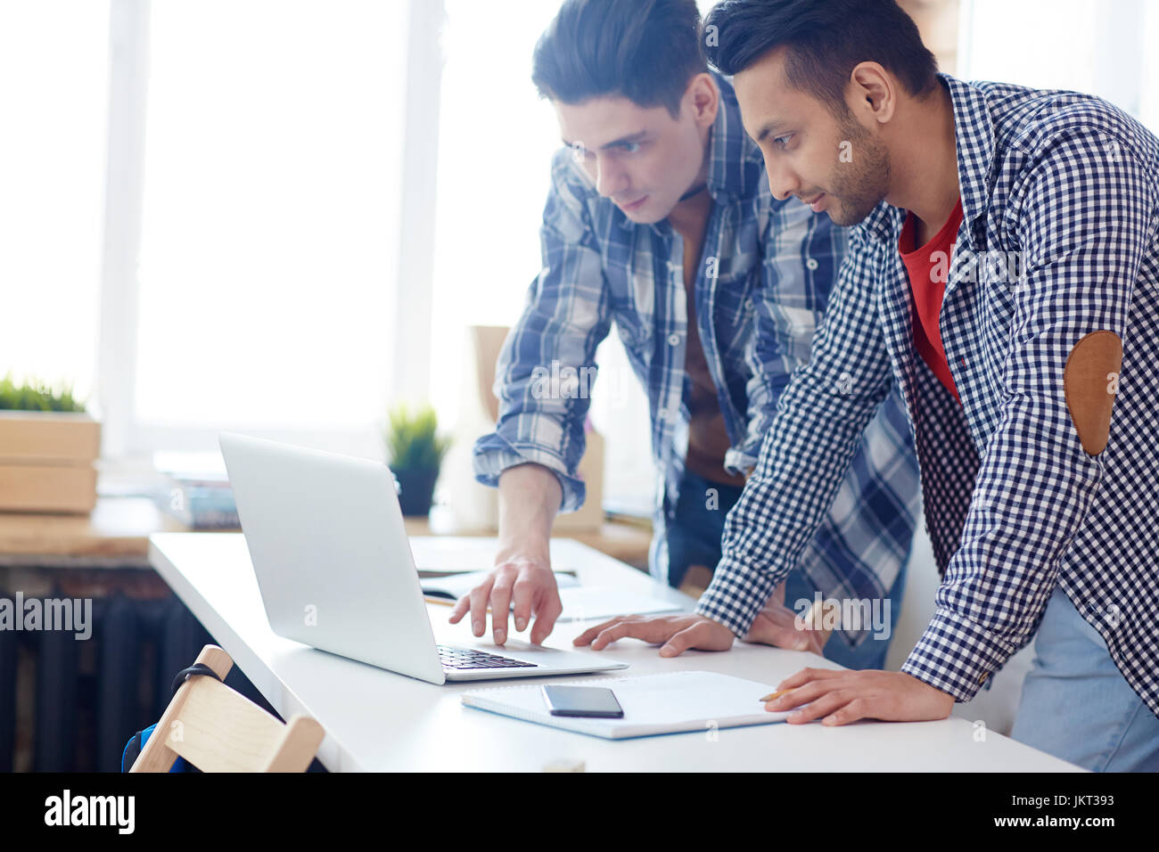 Clever guys reading online data while preparing for conference or exam - Stock Image