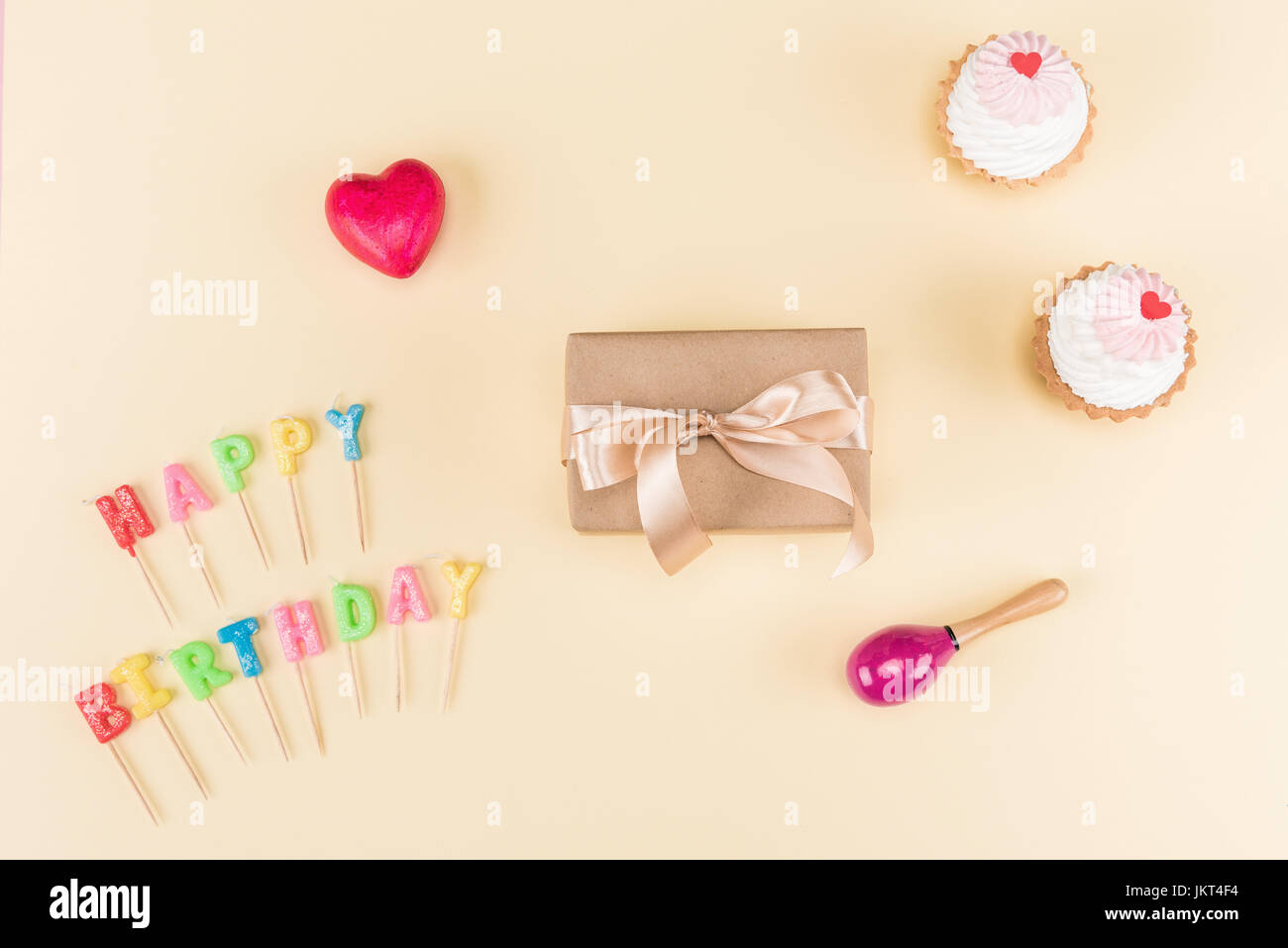 Top view of happy birthday lettering, envelope with ribbon and delicious cupcakes on pink, birthday party concept Stock Photo