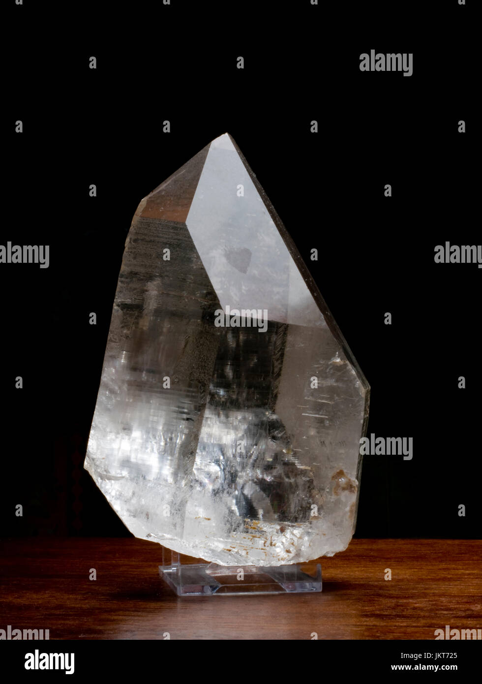 Clear Rock Crystal on a wooden table against a dark background Stock Photo