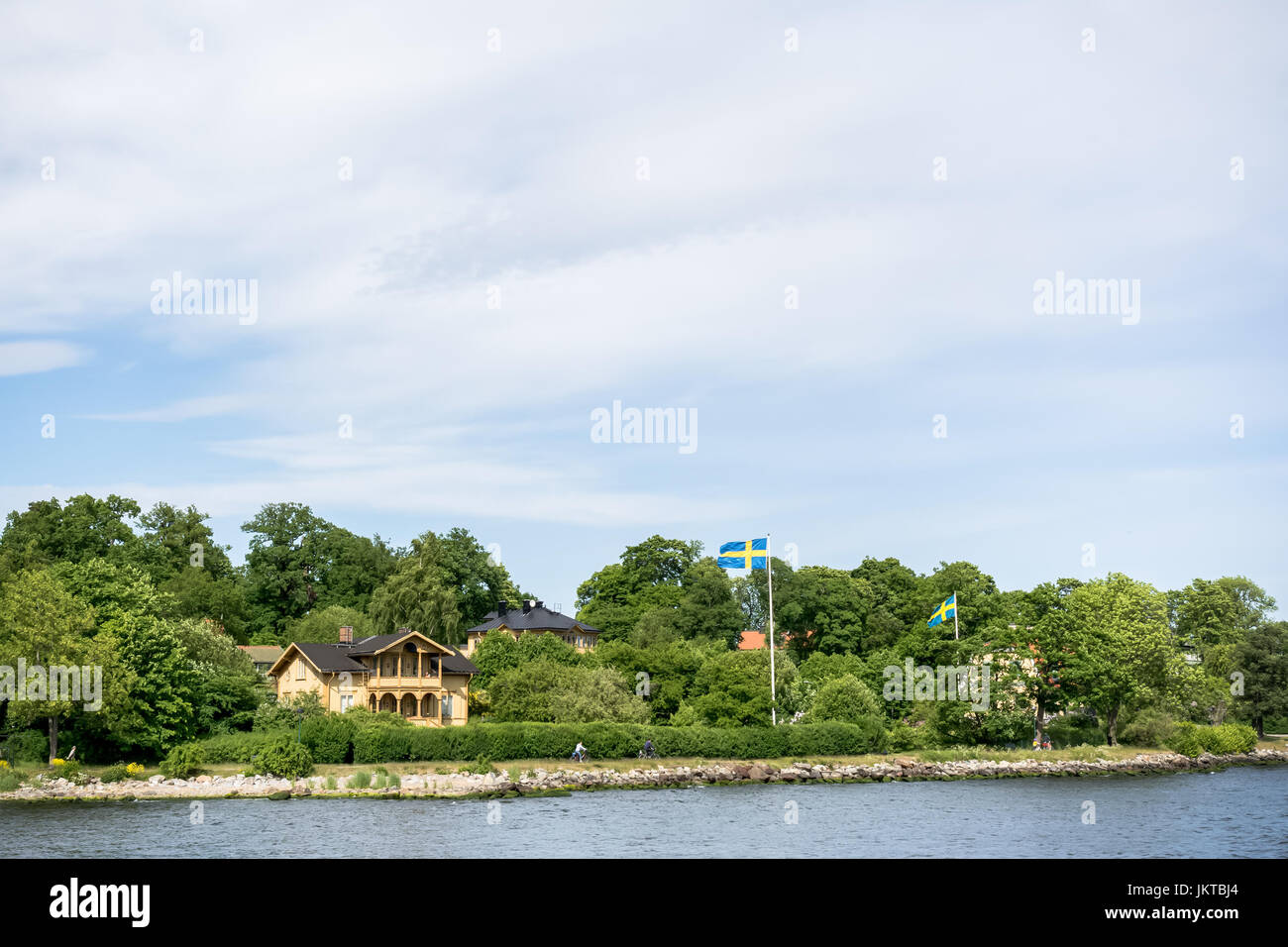 STOCKHOLM, SWEDEN - JUNE 6, 2016: Coastal houses with Swedish flags and cycling people, on an island of Stockholm - Stock Image