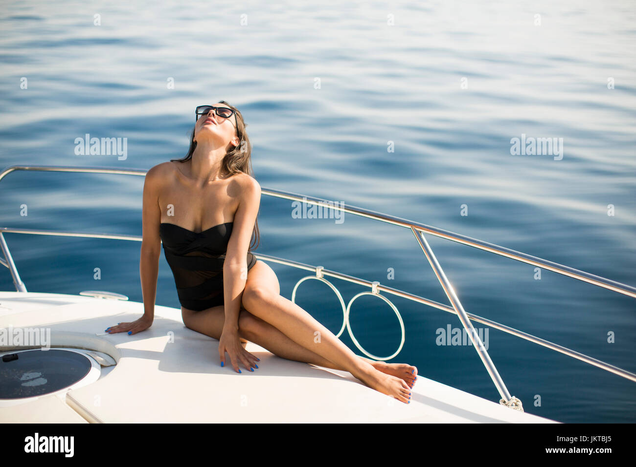 Pretty young woman relaxing on the yacht at sea - Stock Image