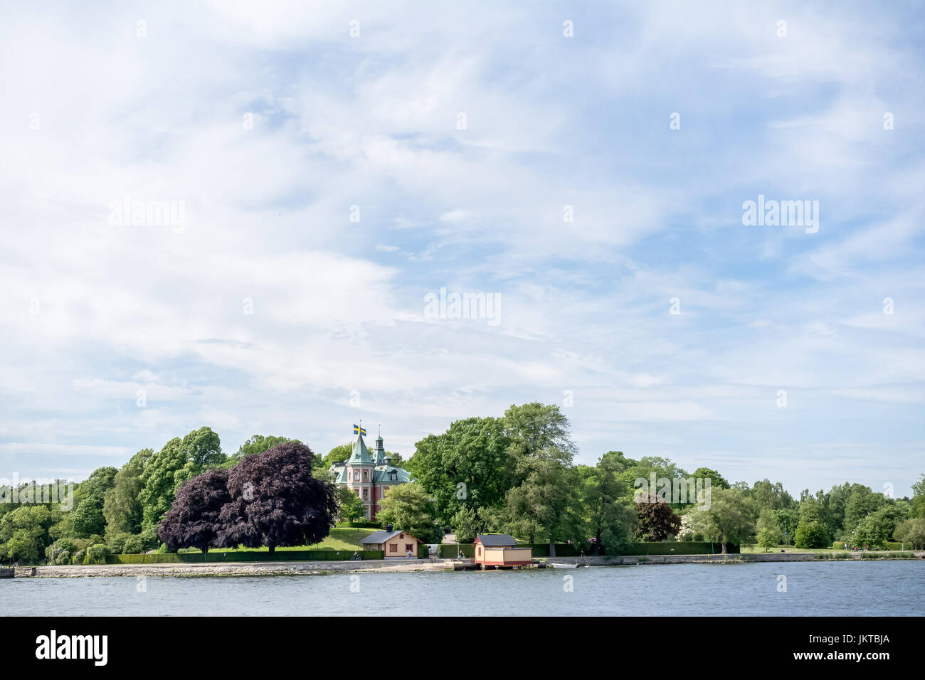 STOCKHOLM, SWEDEN - JUNE 6, 2016: Coastal view of an old small castle with Swedish flags on an island of Stockholm - Stock Image
