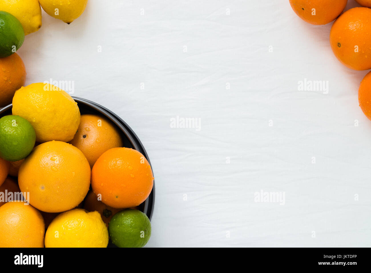 Bowl with different types of whole citruses: oranges, grapefruits, limes and lemons on white cloth background with - Stock Image