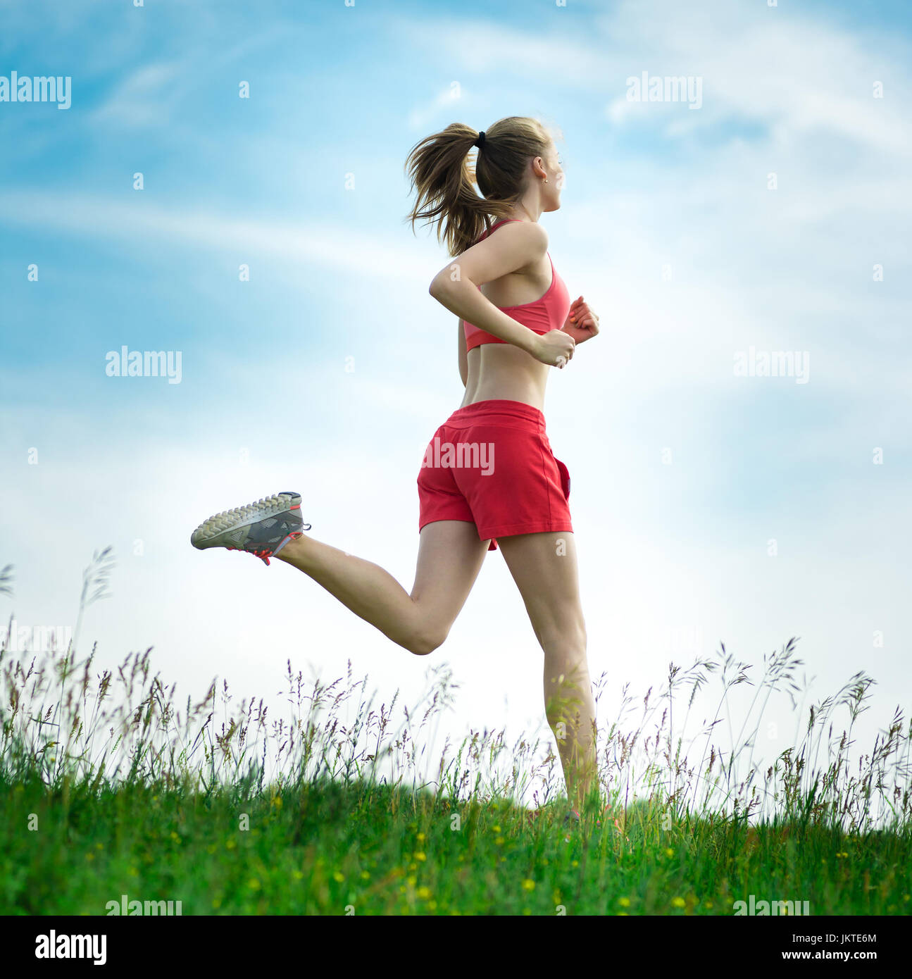 Young lady running. Woman runner running through the summer park rural road. Workout in a park. Beautiful fit girl. Stock Photo