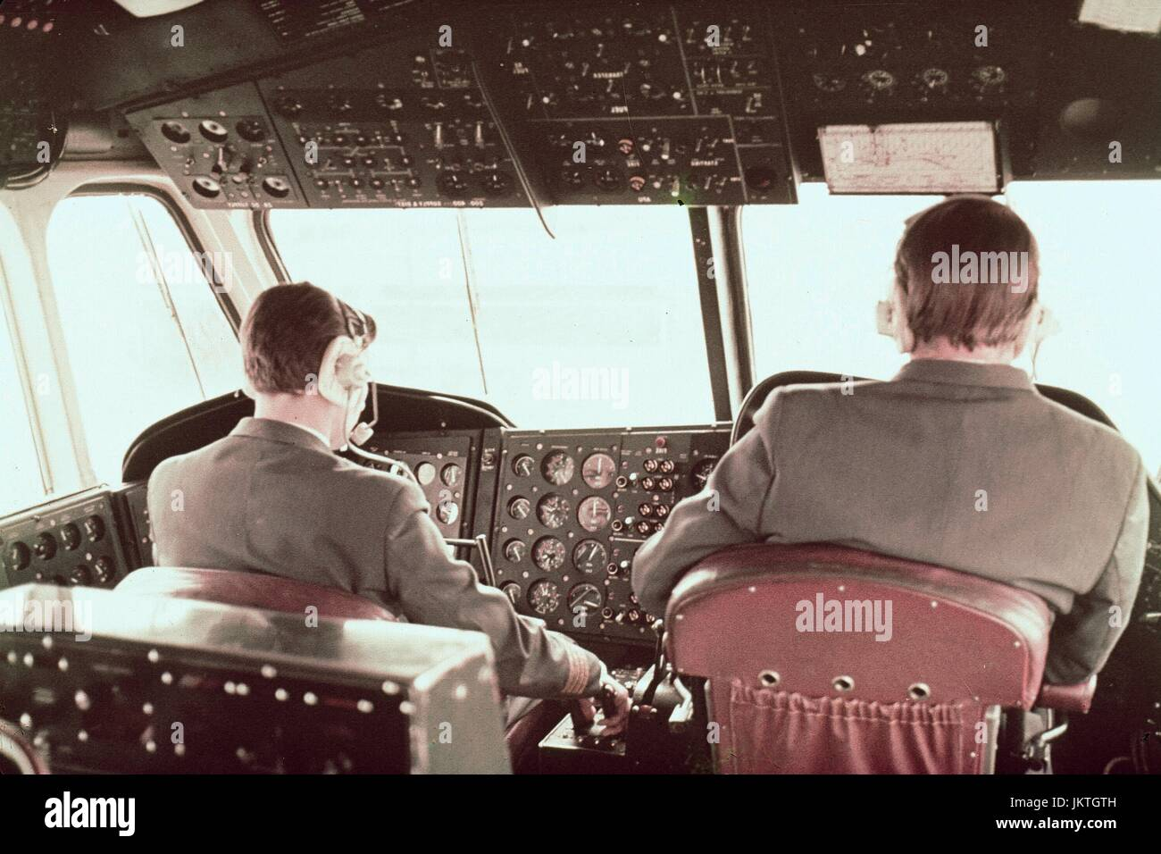 Two formally-dressed pilots wearing communications headsets sit in the cockpit of a passenger airplane, with one Stock Photo