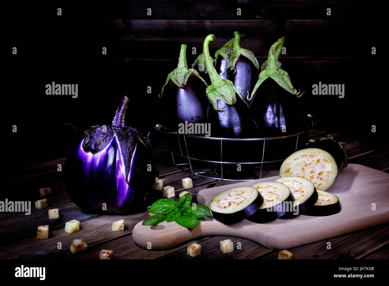 Close up of fresh purple whole eggplant and sliced over an aged wood table. Photographed with light painting technique. - Stock Image