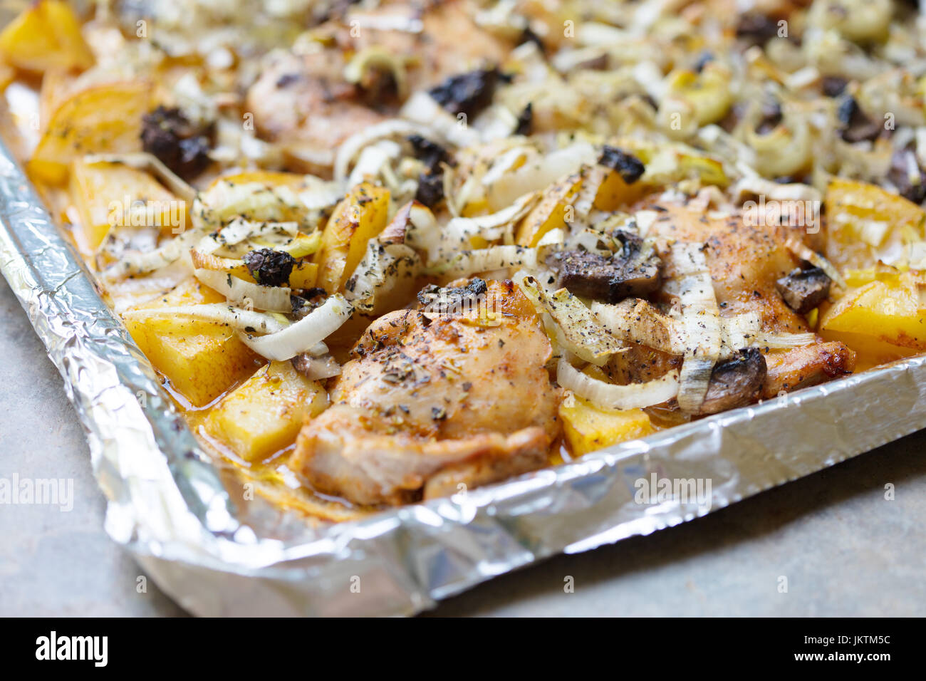 Oven roasted chicken thighs and yukon gold potatoes with leeks and herbs on a baking sheet lined with aluminum foil - Stock Image