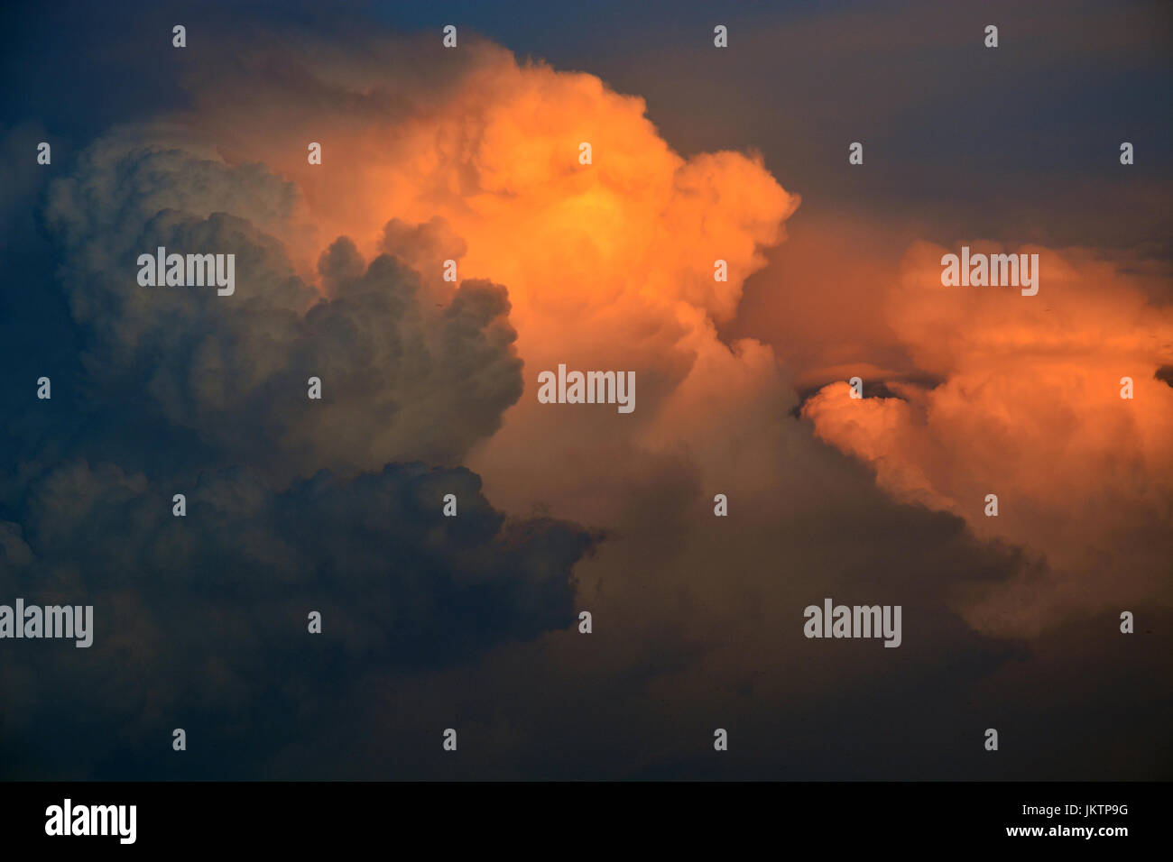 Distant thunderheads over Dallas Texas have an orange glow due to the setting sun. - Stock Image