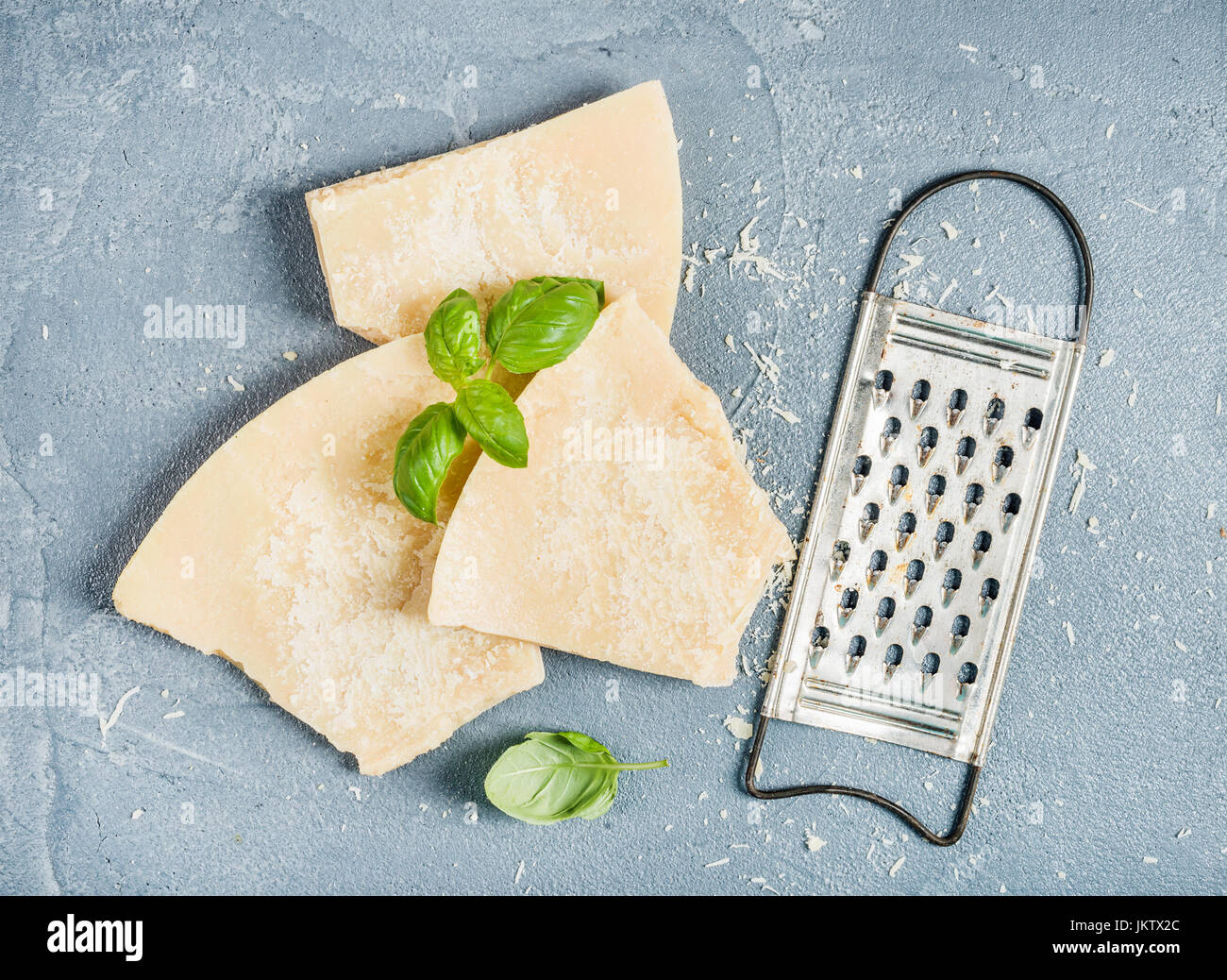 Cuts of Parmesan cheese with metal grater and fresh basil over concrete textured background - Stock Image