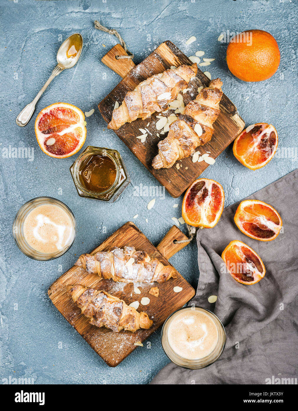 Traditional Italian style home breakfast. Latte in glasses, almond croissants on rustic wooden boards and red bloody - Stock Image