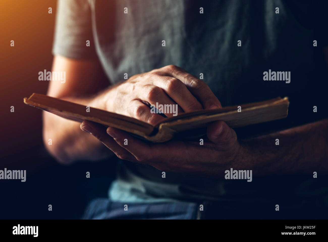 Reading an old book, close up of male hands flipping vintage weathered book pages - Stock Image