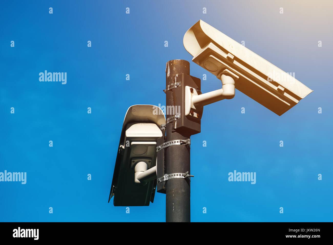 CCTV camera, modern era anti-terrorist electronic surveillance security cameras against blue sky that symbolizes - Stock Image
