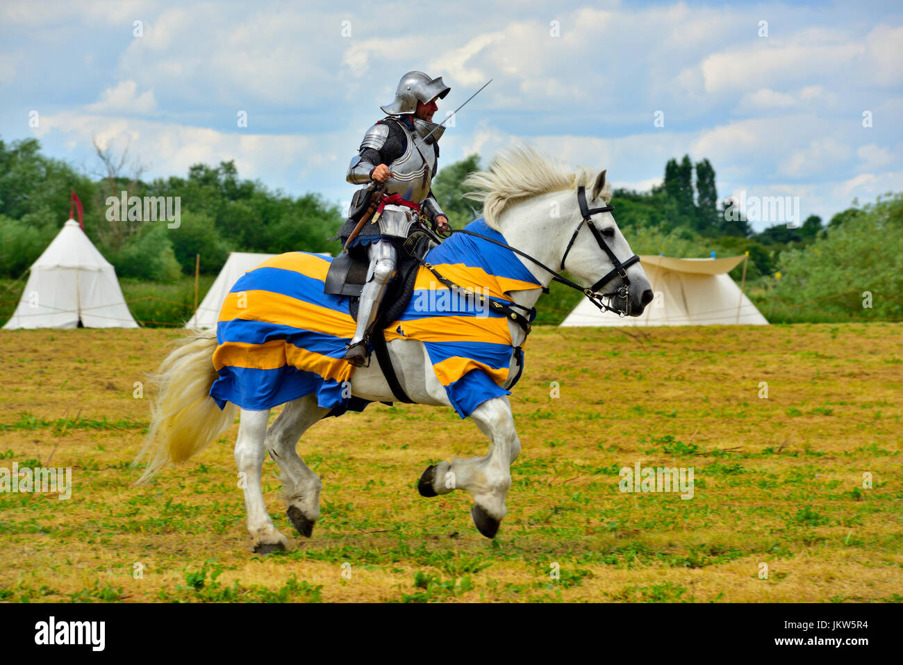 Medieval Knights in full plate armour with sward galloping on horseback - Stock Image