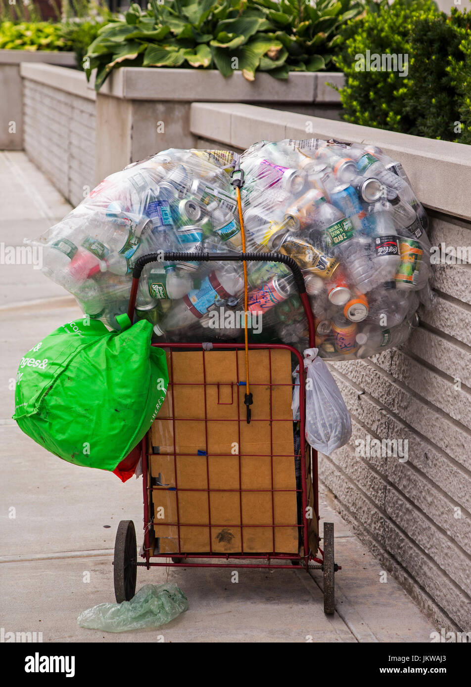 Shopping cart with aluminum cans and plastic bottles ready to be recycled - Stock Image